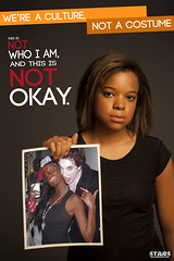 A young, unsmiling black woman holds up a picture of a white woman in black face at a Halloween party. The poster reads We're a culture, not a costume. This is not who I am and it is not okay.