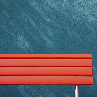 Red bench blue wall