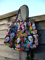 Calaveras Handbag on my fence (SewHappyGeek) Tags: diadelosmuertos calaveras pleatedhandbag alexanderhenryfabric