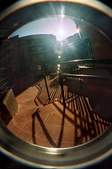 Just Before the Sun Dips Over the Wall... (lefeber) Tags: california city urban building film architecture backlight fence losangeles lomo lomography shadows angles courtyard fisheye lensflare railing angled marinadelrey