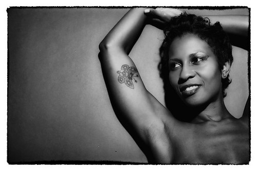 black and white photo of Essence, a black woman, smiling and leaning against a wall