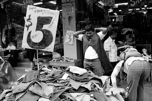 Man sizing up a pair of jeans. Little India, Singapore