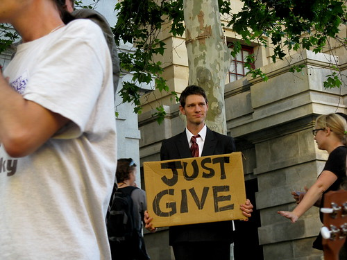 A man in a suit holding a sign reading, 'Just Give'.