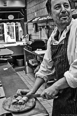 The Butcher Of Edis. #3 (MFotography*) Tags: portrait bw window glass smiling price digital laughing photoshop canon bag table eos counter knife sausage stranger apron shelf butcher tiles list till scales pies cutting ely roll ef28135mm pasties preparing butchers porkpie 500d edis