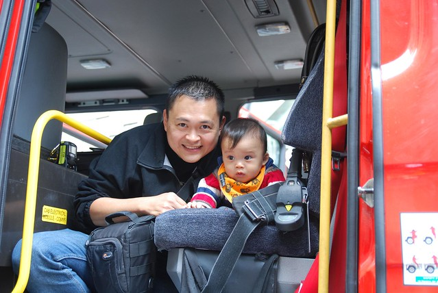 Isaac and daddy in the fire engine - close - photo by Julia