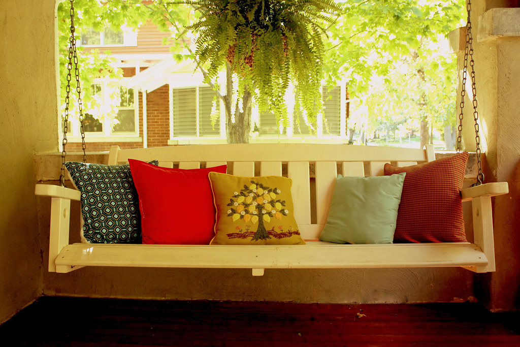 a porch swing of thrifted pillows