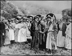 Crowd by caravans (Tyne & Wear Archives & Museums) Tags: family carnival portrait blackandwhite baby home field community fairground circus patterns travellers headscarf walkingstick nostalgic historical caravan shawl tradition generations gypsy period youngwoman gypsies sentimental elderlywoman documentaryphotography archivephotograph