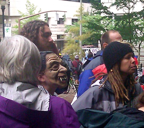 An Occupy Portland protester in a crone mask in the crowd