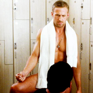 Ryan Gosling with a white towel around his neck and a necklace on standing naked in front of Steve Carrell in Crazy Stupid Love