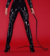 a white woman from the waist down wearing vinyl pants and holding a whip