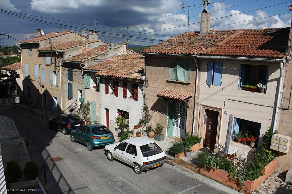 Les maisons en Provence sont simples, avec leurs façades dépouillées et leurs toits en tuile. Toutes sont mitoyennes, dans ces rues du village. Souvent, une marquise protège l'entrée.