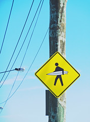 Beach life is so dangerous (Steve Taylor (Photography)) Tags: newzealand christchurch sign yellow surf crossing canterbury surfing pole amarillo nz southisland newbrighton surer