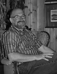 A black and white photograph of a smiling, bearded man, sitting in a chair in front of a wood wall.