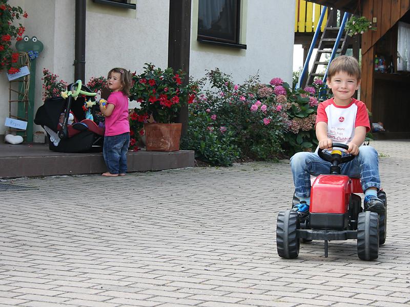 Kind auf einem Kindertraktor