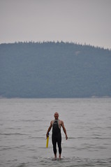 A man in a dry suit stands on a rock on Lake Superior, looking like he is standing on the surface of the water.