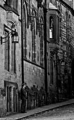 Waiting's The Job. (MFotography*) Tags: street old windows bw man hat digital canon buildings eos town path suit lamps ef28135mm coventry chauffeur 500d