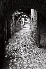 Empty view (Follow The Swallow) Tags: camera old blackandwhite france mountains castle architecture analog rural vintage lens french unsafe spain alley noir village darkness noiretblanc pavement military south lot medieval oldschool backstreet unesco hills cobblestone 55mm knights alleyway citywalls paving ruelle fortification sick chevalier uphill chteau blanc ilford fp4 fujica st705 monte saintcirqlapopie battlement 46 tourisme montagnes narrowstreet remparts colombage 125 patrimoine pavs rampart collines mdieval moyenage midipyrnes halftimbering ditches douves patrimony lotvalley hritage oubliettes btisse blackalley valledulot culturalinheritance architectureditch
