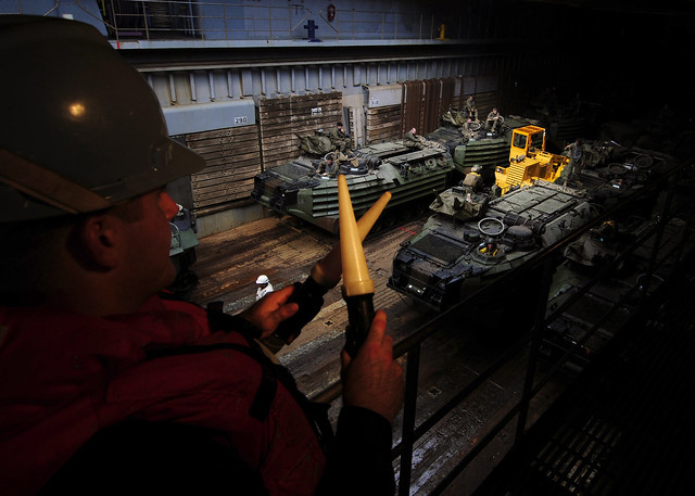 Seaman Henry Stumpf directs an amphibious assault vehicle assigned to the 31st MEU in the well deck of USS Germantown