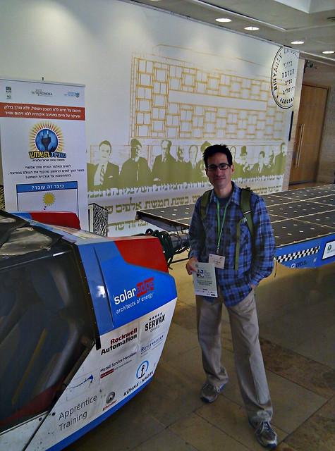 עושה פוזה מול המונית הסולארית של לואיס פאלמר בכנס אנרגיה וסביבה בירושליים