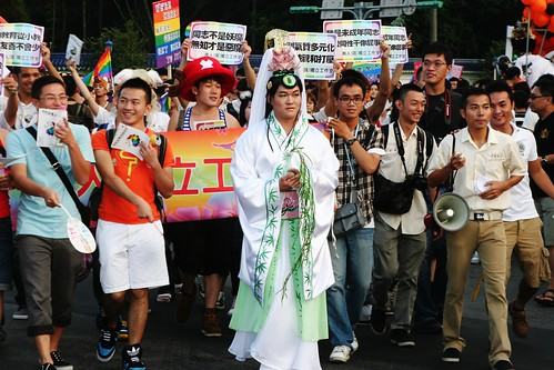 Some religious group are against informing youth about LGBT in schools. A parade participant plays 'Guanyin (觀世音菩薩)', a bodhisatta regarded as both male and female, to demonstrate that 'even gods can be LGBT'.