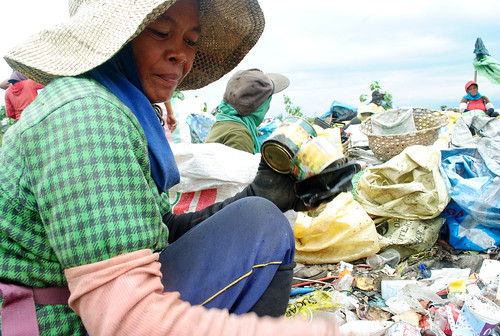 A woman scavenger picks tin cans from the unsegregated bunch of garbage at the Inayawan landfill.