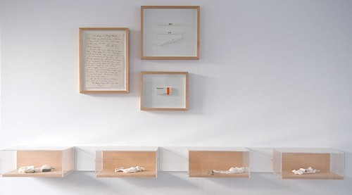 small boxes against a wall with some framed documents