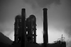 the factory (StephenCairns) Tags: blackandwhite bw rain japan crossprocessed factory explore powerlines smokestacks gifu stacks f63 heavyrain motosu cementfactory wetwindshield canon50d 70200mmf4isusm sumitomocement