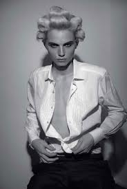 super model andrej pejic in dossier journal with hair curled on top of his head wearing an unbuttoned white shirt and dark trousers