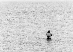 The Fisherman (Luziferian) Tags: ocean sea blackandwhite bw man blancoynegro water canon eos fisherman meer alone noiretblanc baltic nb bn sw lonely angler 500d schwarzweis 18135mm blk tpablackwhite