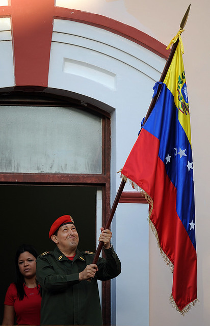 Presidente Chávez Frías en el balcón del pueblo iza la bandera