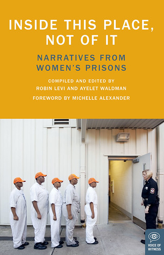 the cover of Inside This Place Not Of It. It features a scene from prison, five black women wearing white jumpsuits and orange hats. The stand single file and face a white female office in a blue uniform. Even though they are standing in subordination, there is dignity in the way they hold themselves.