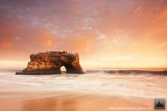 Bridge Into The Sun - Natural Bridges, Santa Cruz, California (david.richter) Tags: ocean california statepark pink sunset red summer orange usa santacruz seascape fall monument nature water northerncalifornia canon wonder landscape eos rebel gold twilight raw waves sundown pacific outdoor dusk hiking unitedstatesofamerica salmon hike adventure norcal polarizer rare circular graduated naturalbridges manfrotto kalifornien xsi rushing happydance magiclight giottos gnd goldencoast rainshowers singleexposure ishootraw nohdr davidrichter singhray 450d nofog aftersundown gradualneutraldensityfilter northofbigsur wwwdavidrichterphotographycom nomarinelayer glowlikeyoumeanit