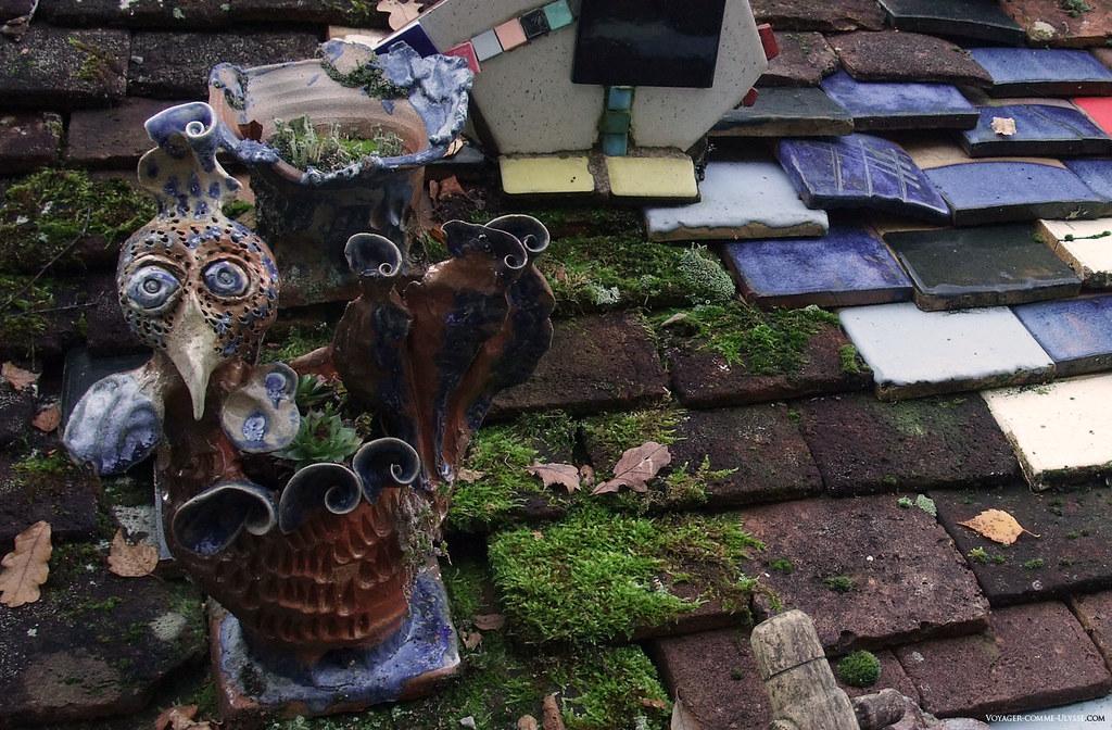 Une poule sur un toit, qui transporte sur son dos des joubarbes, au milieu de toutes ces couleurs