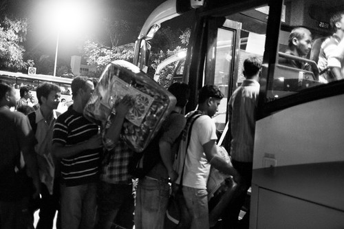 A man carrying a load boarding the bus with other foreign workers.