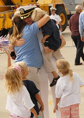 Cmdr. George Kessler, executive officer of USS Spruance is reunited with his family after Spruance arrived in San Diego