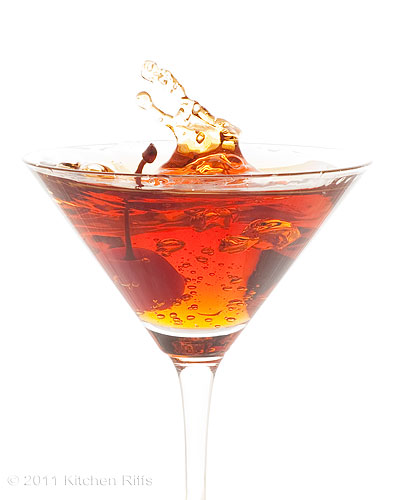 Splashing a cherry into a Manhattan Cocktail