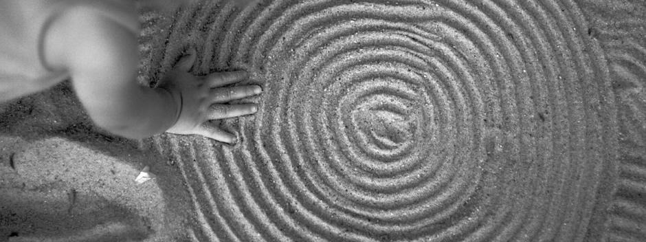 Fotografía en blanco y negro de un niño jugando con sus manos sobre arena en forma de anillos