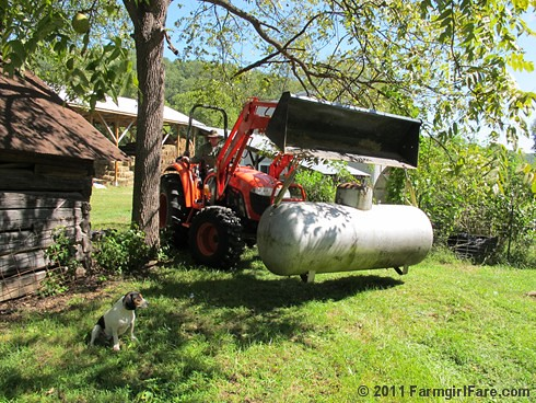 Joe uses the tractor to move the propane tank - FarmgirlFare.com