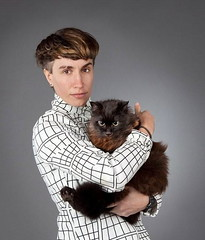 Tender Forever, a white woman with short brown hair, holds a cat and looks at the camera