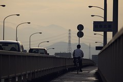the ride home (StephenCairns) Tags: bridge boy mountain mountains wet bike bicycle japan streetlamps streetlights highschool explore powerlines commute teenager f56 puddles fp frontpage gifu commuters lampposts hydrotower hydrolines mudpuddles highschoolstudent canon50d 70200mmf4isusm
