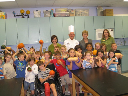 Deputy Under Secretary Janey Thornton (center right) and American Culinary Federation Chef David S. Bearl (center left) pose with RB Hunt Elementary first graders from Christine Skipp's and Lori Hall's class as they show off pumpkins. Thornton and Bearl visited the school located in St. Augustine, Fla., on Oct 18, to celebrate Farm to School Month and First Lady Michelle Obama's Let's Move! Chefs Move to Schools initiative. The pumpkins were harvested from the University of Florida's Institute of Food and Agricultural farm, Hastings, Fla., and were also used in the school's lunch for the day. (Photo by Lanna Kirk)