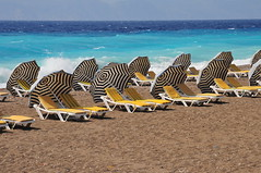 Stripey Sun Umbrellas (Bradclin Photography) Tags: windyday rhodes emptyseats travelphotography beachumbrellas movementandmotion notakers yellowbeachchairs stripeyumbrellas travelrhodes whatevertheweathercatchycoloursstripes
