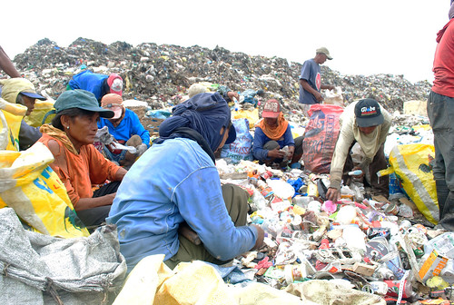 A group of women surround the unsegregated bunch of garbage at the Inayawan landfill to pick cans, aluminums and plastic bottles.