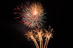 Red and orange fireworks, two large circular bursts on top, with three smaller bursts underneath, joined by pillars of light.