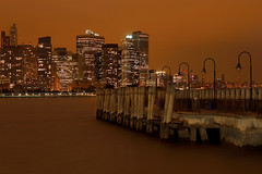 Pumpkin Spice (SunnyDazzled) Tags: statepark city nyc newyorkcity longexposure autumn orange newyork lamp rain skyline night liberty lights bay harbor amber pier newjersey warm glow cityscape skyscrapers cloudy lighttrails posts ferrydock