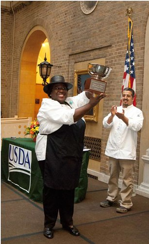 Caption 1: Chili champion, Shirley Brown accepting the silver chili bowl trophy at the 2011 Hispanic Heritage Food Fiesta. In the background is Chef Pedro Matamoros applauds Shirley's victory.