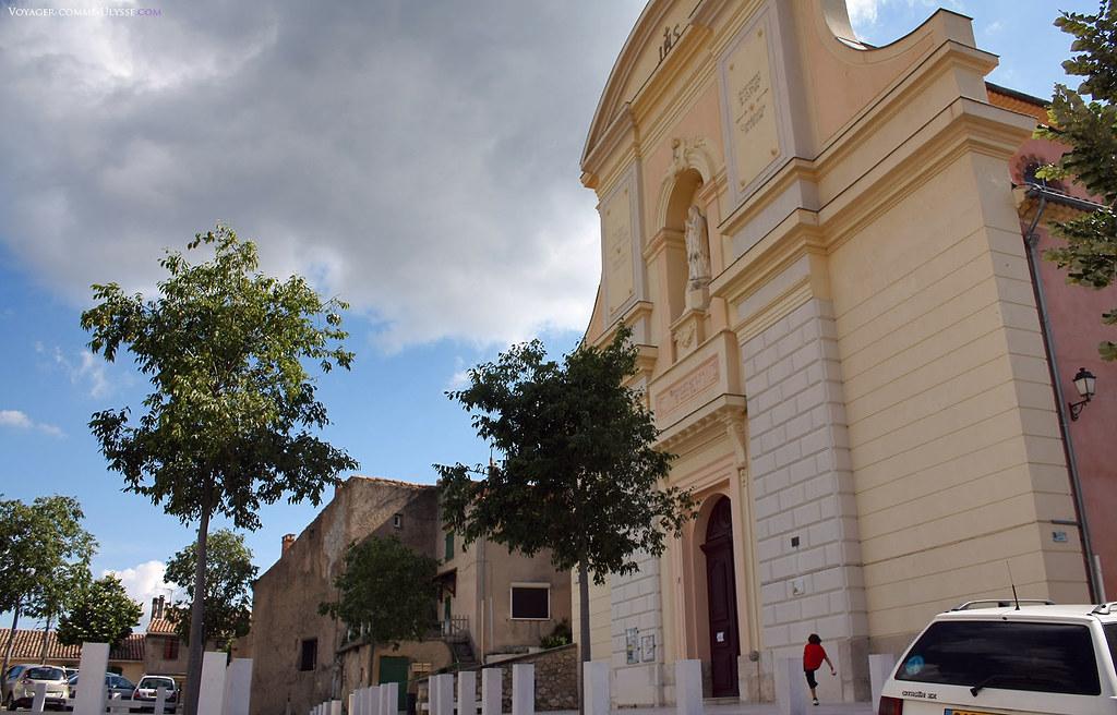 Devant l'église du village, les enfants jouent au ballon. La première pierre de cette nouvelle église fut posée en 1853.