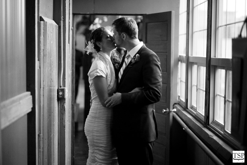 Bride and Groom Kiss in Hallway