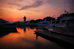 Harbour Town Lighthouse at Sunset (Seth Oliver Photographic Art) Tags: clouds reflections boats landscapes iso200 nikon dusk southcarolina silhouettes sunsets sunsetglow sailboats harbors beautifulclouds pinoy 30secondexposure marinas longexposures hiltonheadisland travelphotography harbourtown beautifulskies d40 wetreflections sunsetreflections sunsetskies caliboguesound wbauto vacationshots harbourtownlighthouse sunsetshots goldensunsets perfectsunsetssunrisesandskys sunsetimages manualmodeexposure harbourtownmarina setholiver1 bwnd10stopfilter aperturef220 18105mmnikkorlens timedelaytriggeredshot ballheadtripodmuntedshot daytimelightexposures