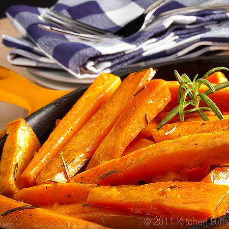 Roast sweet potatoes with rosemary garnish in yellow enamel skillet, forks and napkins in background